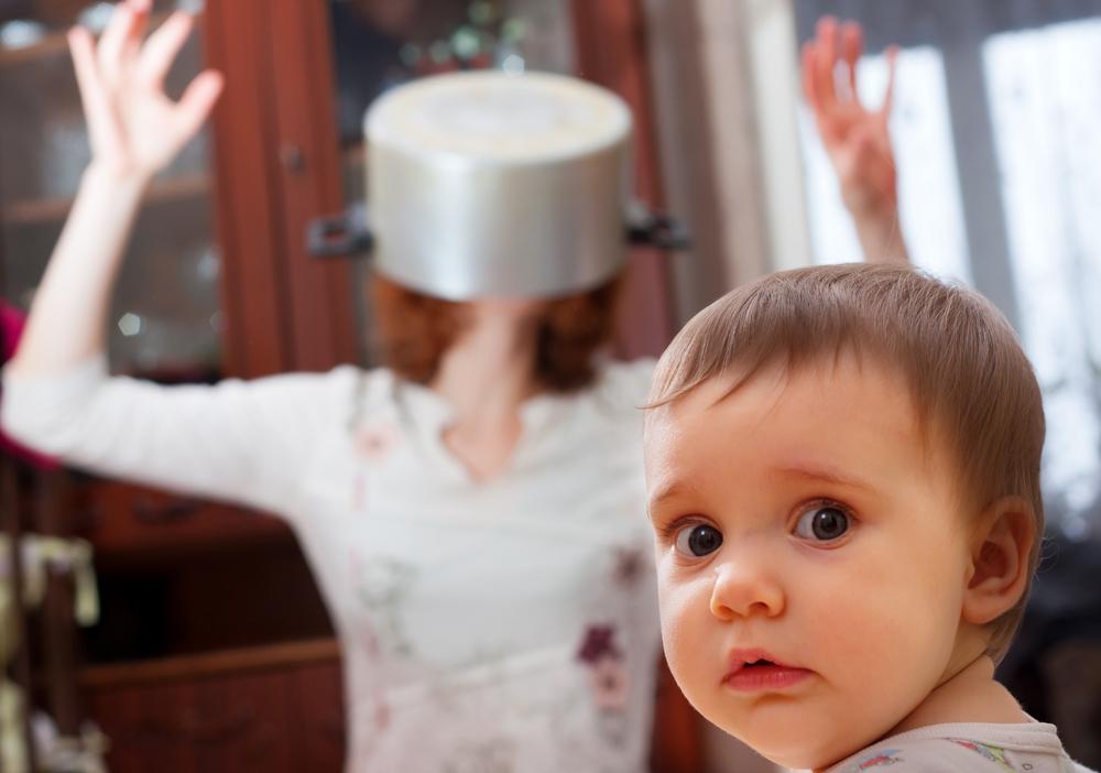 Bebe en primer plano y su madre con una olla en la cabeza en segundo plano