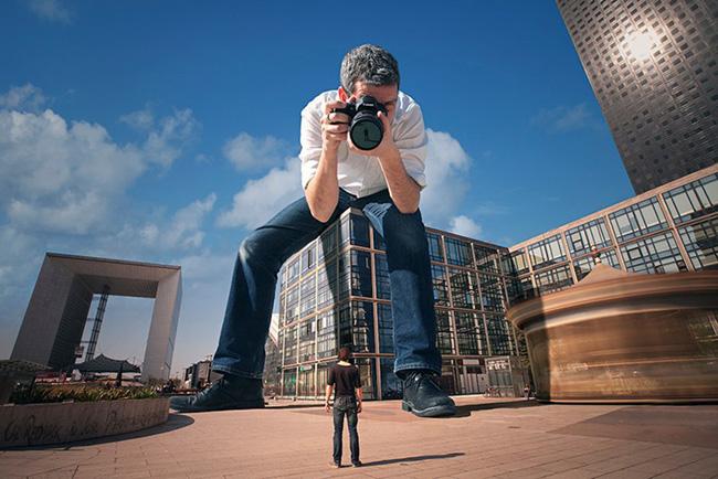 Hombre sentado sobre un edificio sacando una foto a una persona a escala y altura normal