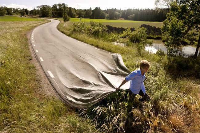 Hombre corriendo por el campo llevándo consigo la autopista en sus manos.