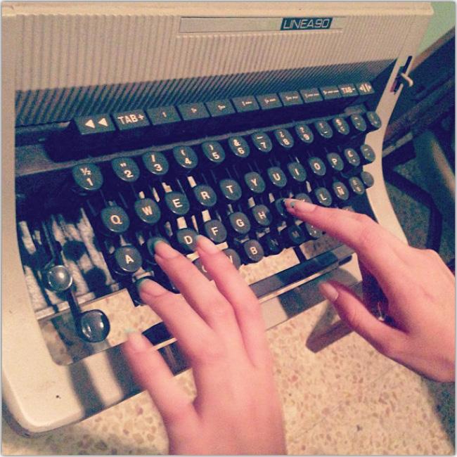 Máquina de escribir, se ven dedos escribiendo en el teclado de ella.