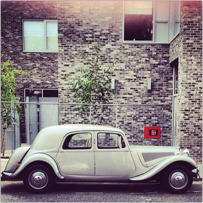 Vista de un auto antiguo con un muro de ladrillos grises de fondo.