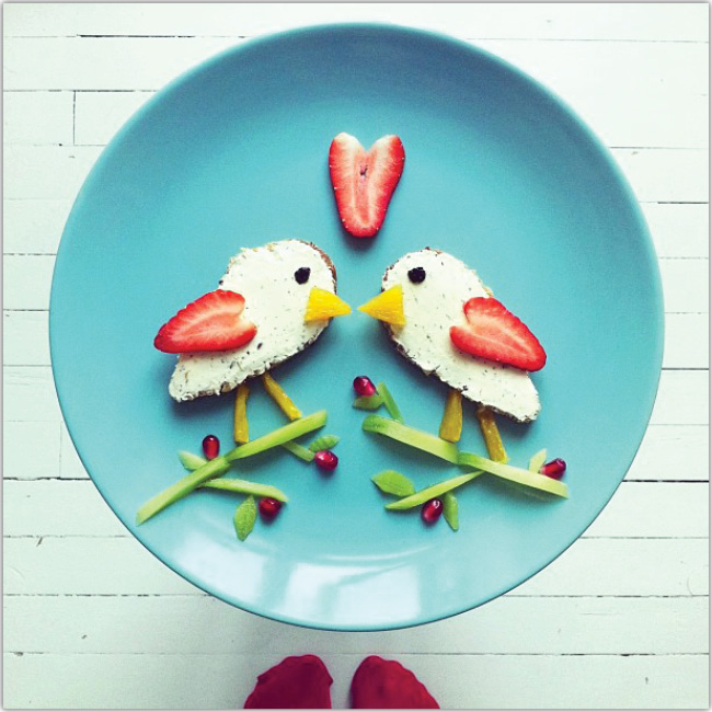 Plato de comida decorado con forma de dos pequeños pajaritos besandose.