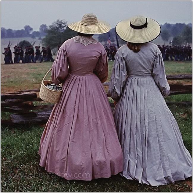 Dos mujeres de gorros y vestidos largos de espalda y mirando como una tropa de soldados antiguos van a la batalla