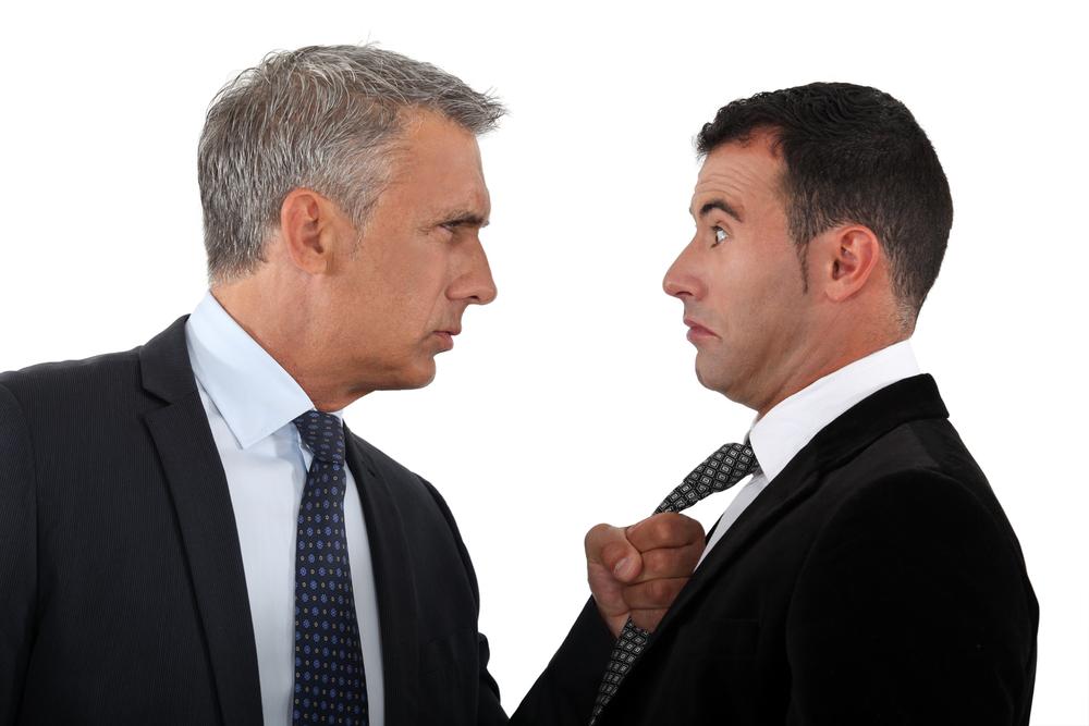 Jefe mirando fijo a un empleado y tirando de su corbata.