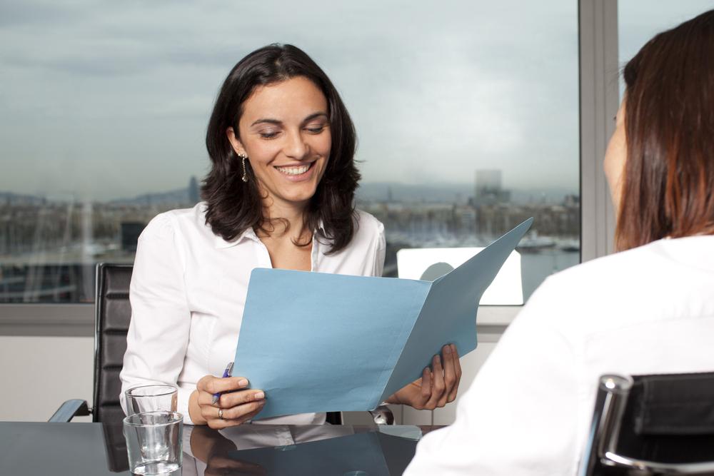 Dos mujeres en entrevista laboral. Una de ellas sostiene una carpeta azul y sonríe.