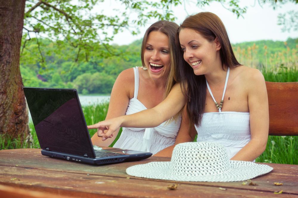 Dos mujeres se ríen mirando y apuntando a una pantalla de computador