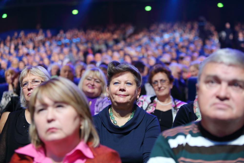 Publico de una obra teatral o película. Todos están enojados menos la persona en foco, quién tiene una leve sonrisa en el rostro