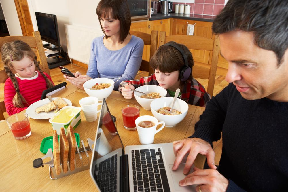 Familia reunida en una mesa. El padre está en el notebook, la madre en su smartphone, la hija en una tablet y el hijo con audifonos wireless.