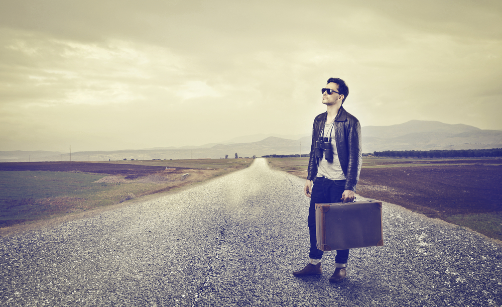 Hombre solo en una carretera con una maleta en la mano