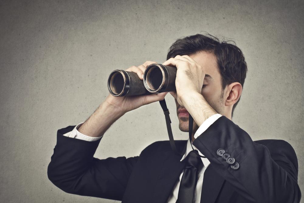Hombre mirando por vinoculares y vistiendo un traje