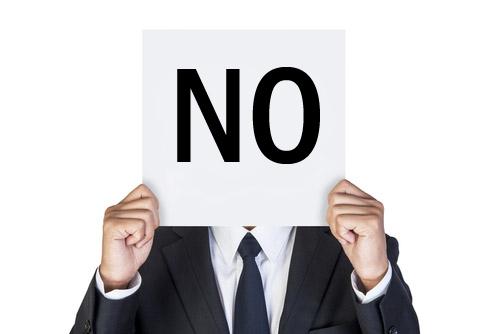 Persona sosteniendo un cartel que dice NO que cubre su rostro