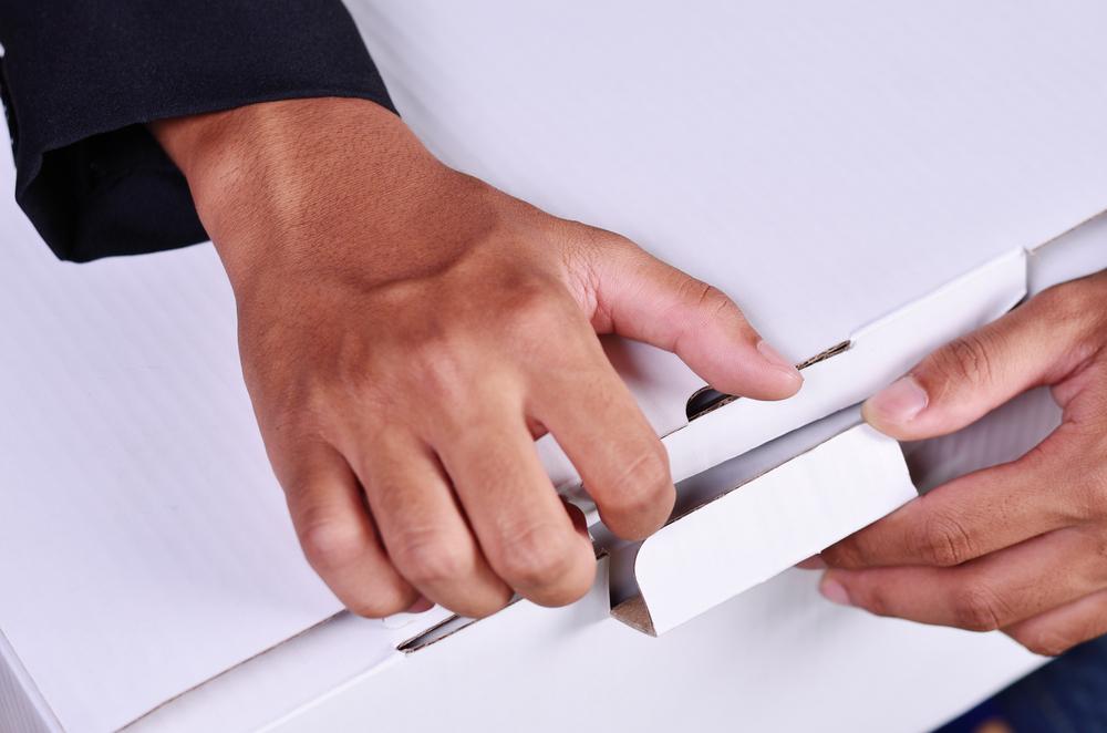 Primer plano de unas manos abriendo una caja