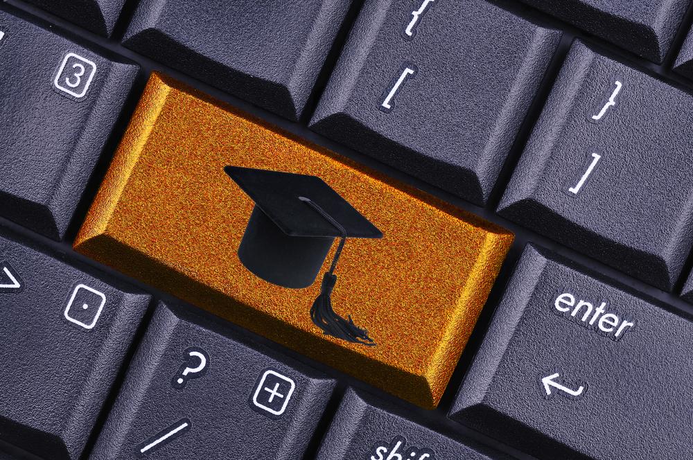 Teclado de computador con una tecla que tiene el ícono del gorro de graduacion