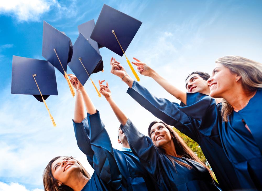 Grupo de estudiantes con toga de graduación lanzando los gorros al aire