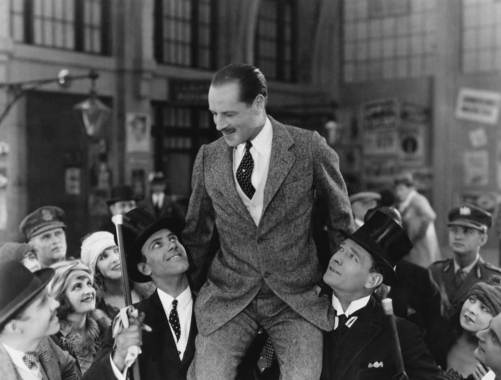 Foto antigua de un grupo de gente levantando y honrando a un hombre y sentándolo en sus respectivos hombros