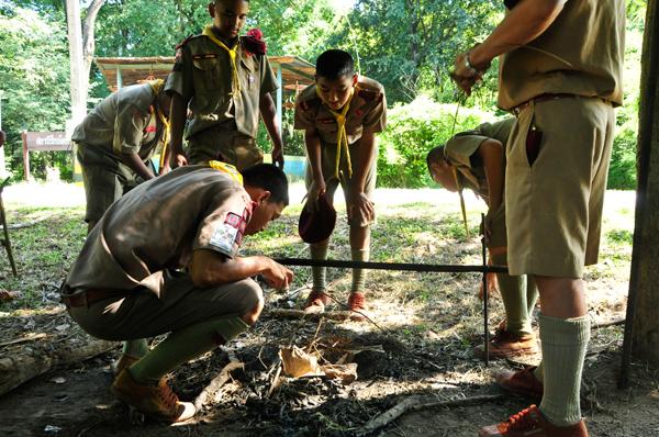 Boy scouts prendiendo fuego en un campamento