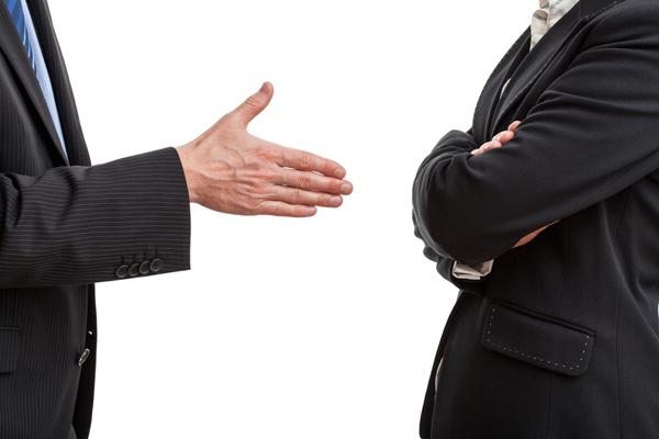 Dos ejecutivos. Uno estira la mano y el otro se niega cruzando los brazos