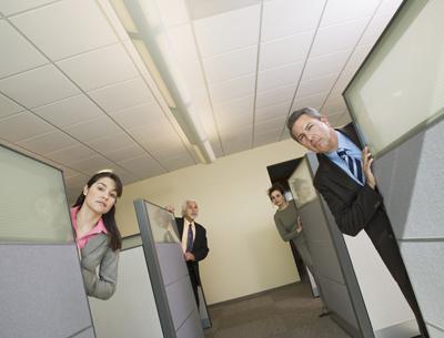 Oficinistas asomando sus cabezas desde sus cubículos