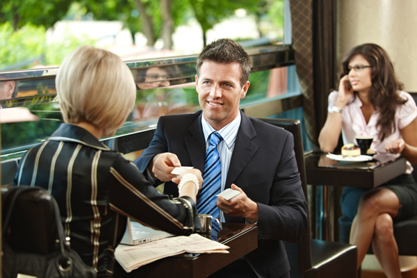 Hombre y mujer sentados en una cafetería. Hombre de corbata le entrega su tarjeta de presentación a la mujer rubia y de cabello corto.