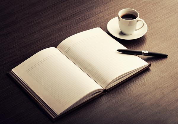 Libreta de notas abierta y vacía con un lápiz encima de ella y una taza de café en el costado