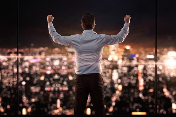 Hombre de espaldas celebrando un triunfo y observando una ciudad de noche