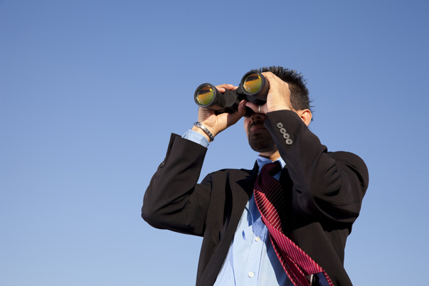 Hombre de traje y corbata mirando por vinoculares