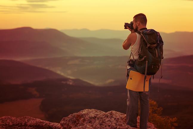 Joven de espaldas en la cima de una montaña tomando una foto del atardecer