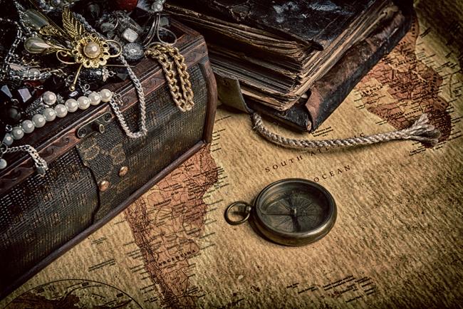 Foto de primer plano de un tesoro y un mapa con una brujula sobre ellos