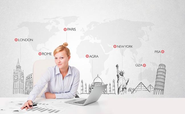 Mujer y su computador con un mapamundo a sus espaldas
