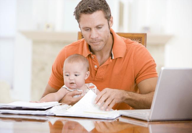 Padre sentado con una computadora y su hija en brazos