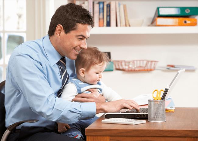 Padre trabaja en su computadora con su hija en brazos